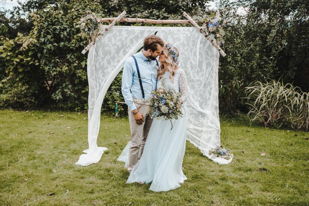 Unterschied Standesamt, Kirche freie Trauung Brautpaar vor Traubogen