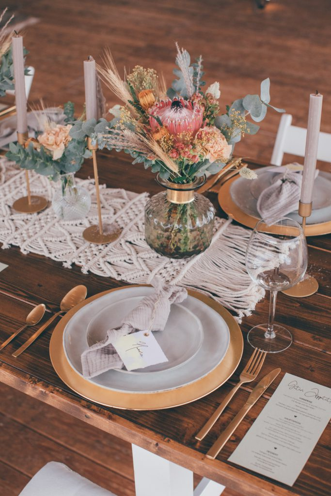 Lässige Hippie Strandhochzeit Tischdeko mit Makramee, Messing, goldenem Besteck und Glas Vasen
