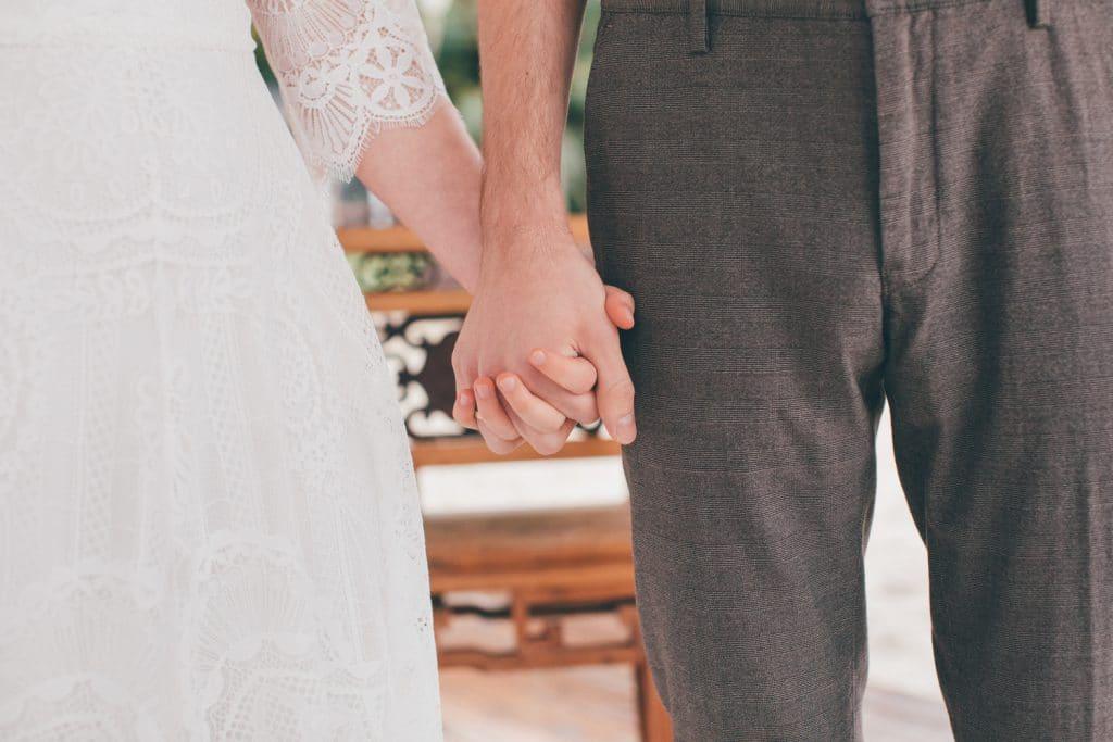 Lässige Hippie Strandhochzeit Brautpaar Händchen haltend