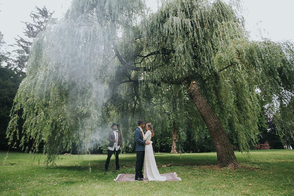 Brautpaar auf Teppich unter großem Baum