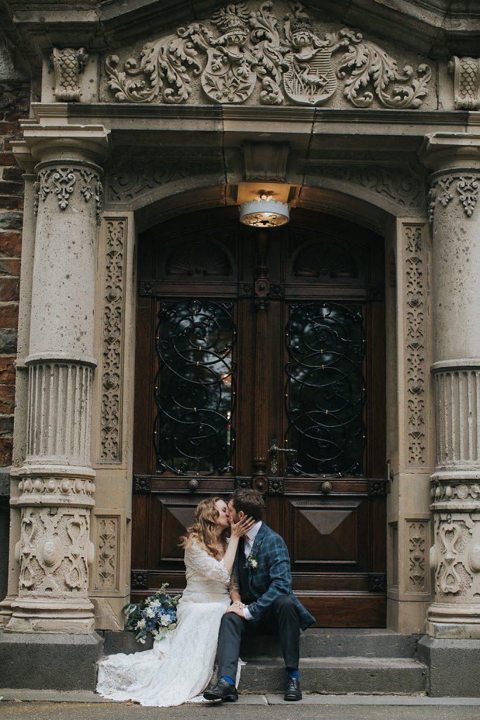 sitzendes Brautpaar vor Holztür