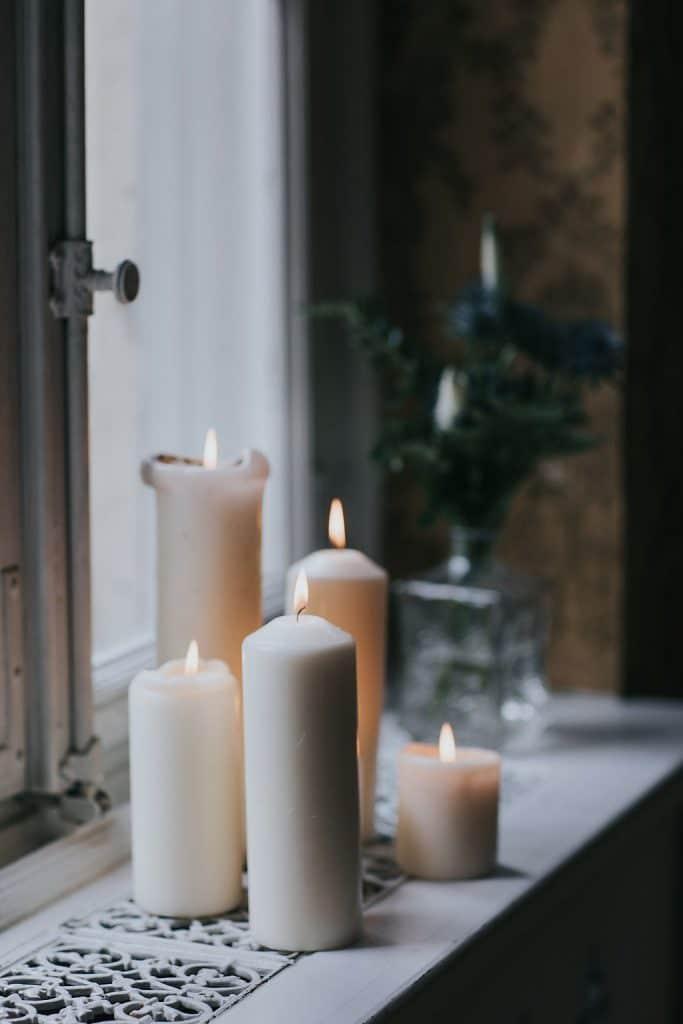 weiße Kerzen auf Fensterbank