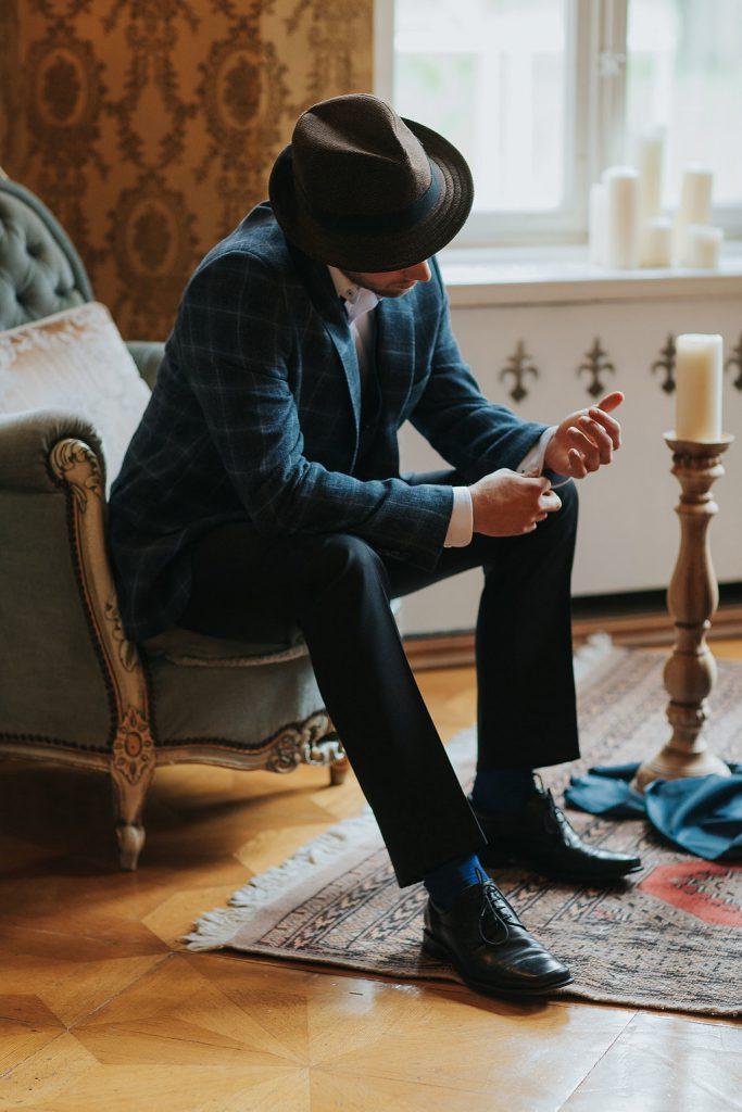 Bräutigam beim Getting Ready auf grünem Sessel