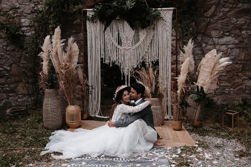 Greenery Boho Wedding - intime kleine Sommerhochzeit unter freiem Himmel Brautpaar vor Makramee Traubogen