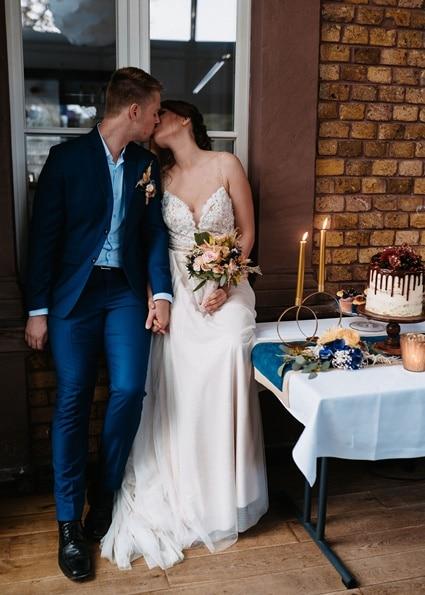Autumn Colors küssendes Brautpaar neben Sweet Table