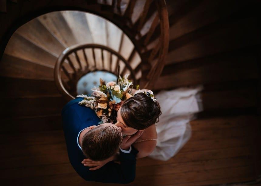 Autumn Colors küssendes Brautpaar Treppenhaus Holz
