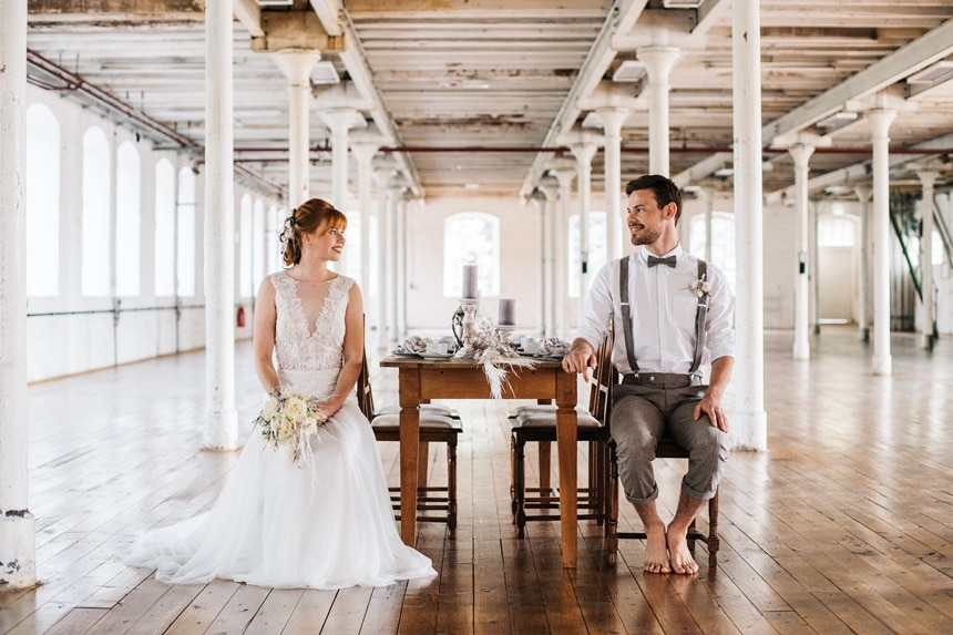 Moho Loft Wedding sitzendes Brautpaar in Loft